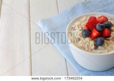Bircher Muesli with Fresh Strawberries and Blueberries on Top with Copy Space Horizontal