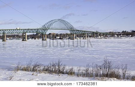 Winter snow scene Centennial Bridge crossing over the Miramichi River, New Brunswick to Chatham with buildings and commerce in the background on a chilly bright blue sky sunny day in February.