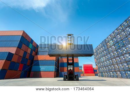 Forklift truck lifting cargo container in shipping yard or dock yard against blue sky with cargo container stack in background for transportation importexport and logistic industrial concept