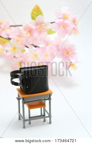 Schoolchild's rucksacks and cherry blossoms on white background.  Black randoseru. Entrance ceremony concept.
