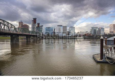 Portland Oregon skyline river bridge with dramatic clouds.