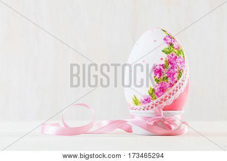 Single easter handmade egg on wooden white table. Decoupage art, floral design