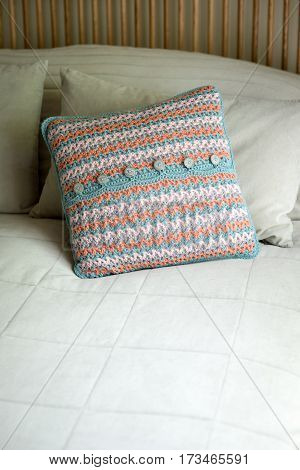 Square Throw Pillow In Crocheted Case On Bed