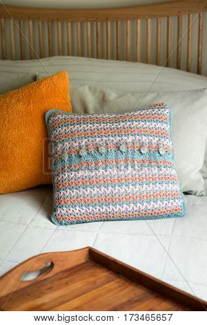 Square Pillows And A Wooden Tray In Bed