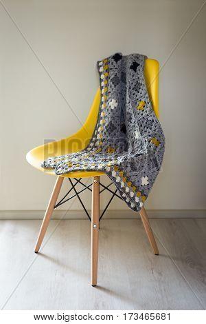 Crocheted mat on a yellow chair still life