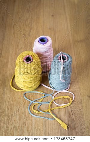 Pink, Yellow, And Gray Yarn In Individual Spools