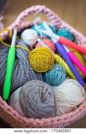 Balls Of Yarn And Crochet Needles In Knitted Woolen Basket
