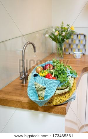 Fruits And Vegetables In Crocheted Bag On Kitchen Counter