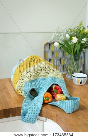 Crocheted Bag Containing Bell Peppers And Apples On Kitchen Countertop