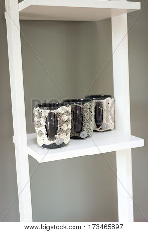 Mugs In Knitted Woolen Covers On White Shelving