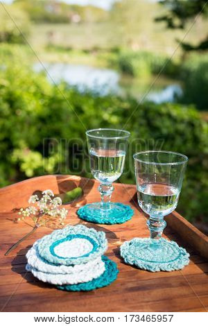 Glass Goblets With Water On Knitted Woolen Coasters