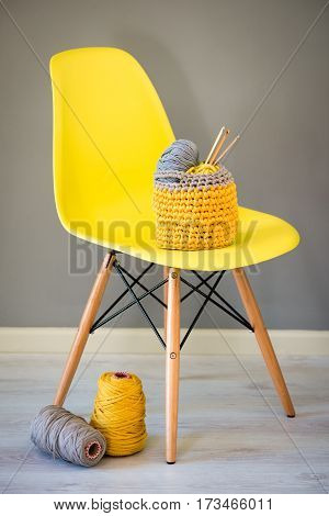 Crochet Needles And Yarn In Knitted Basket On Yellow Chair