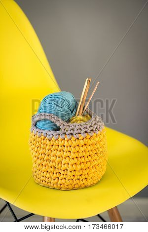 Crochet Hooks And Yarn In Knitted Basket On Yellow Chair