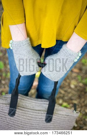 Hands In Knitted Gloves Holding A Woolen Hand Bag