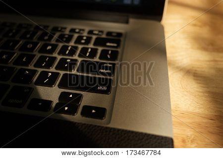Laptop computer keyboard on sunshine on wooden background.