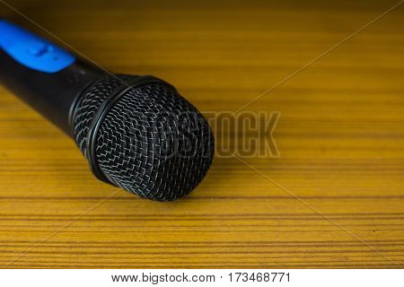 The microphone is placed a wooden table.