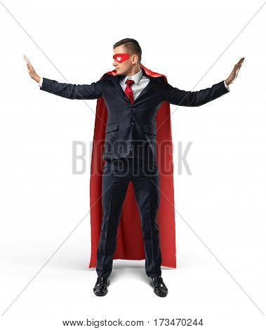 Businessman in a red cape and a red eye mask with hands raised as to stop something on his sides on white background. Business and success. Corporate hero. Superpowers and coaching.