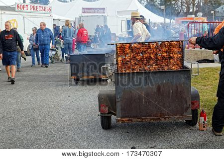 STRASBURG PENNSYLVANIA - February 25 2017: Amish volunteers barbecuing chicken at the annual Spring Sale to benefit the Fire Company. Sale items include quilts antiques crafts food sporting goods tools farm equipment and horses.
