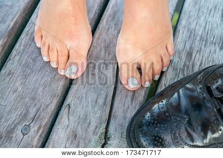 Close up of woman's feet with painted fingernails and black men's shoe on a wooden footbridge