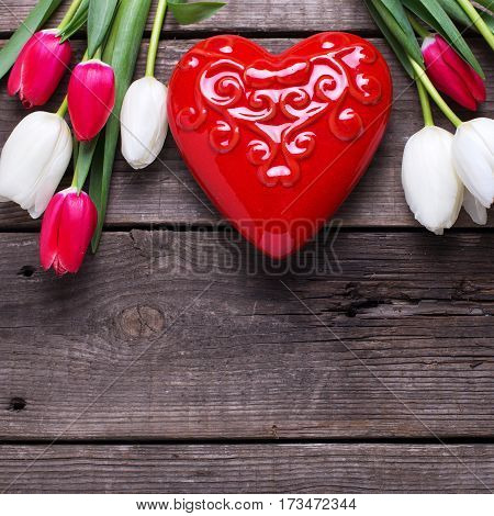 Red decorative heart and bright spring tulips flowers on rustic wooden background. Selective focus. Flat lay. Place for text. Square image.