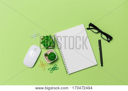 Green Office Desk Table With Grid Note Paper Book, Mouse, Eye Grasses, View From Above In Studio Pho