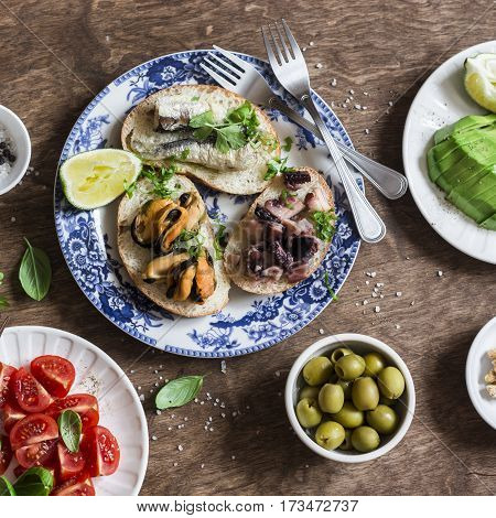 Delicious tapas - sandwiches with sardines mussels octopus grape tomato and avocado on wooden table top view