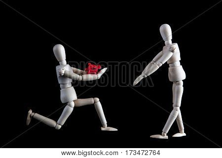 Wedding, Engagement Proposal Or Valentines Concept. Kneeling Wooden Figurine Offering Flower To Stan