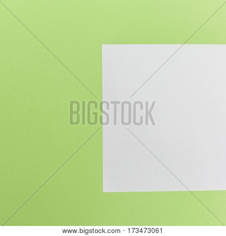 Top View White Paper On Green Background.