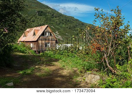 Old wooden house in the brookvalley Spokoyny at the foot of outer north-eastern slope of caldera volcano Gorely.