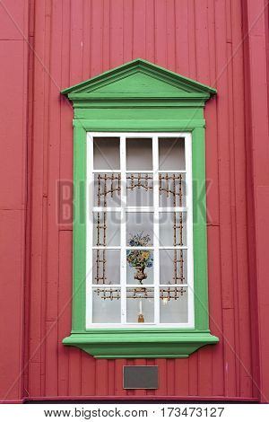 red wall green window curtain vase candle holder