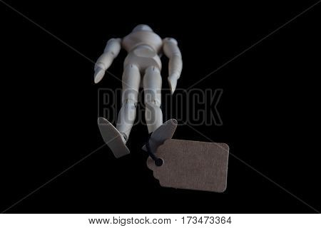 Wooden figurine lying with tag tied to its foot on black background. Shallow depth of field.