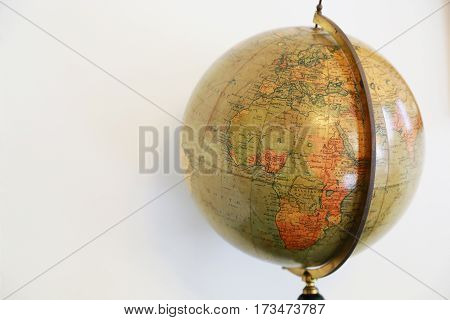 Scene of an old terrestrial globe and the white wall