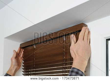 Installing wooden blinds. A man attaches a decorative bar on top.
