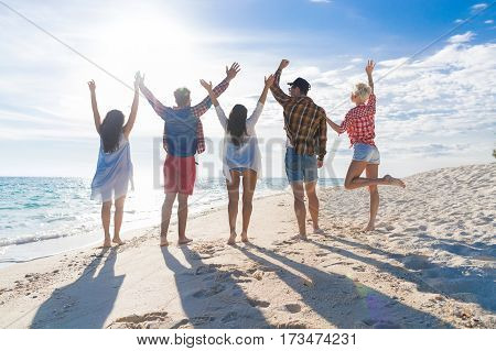 Young People Group On Beach Summer Vacation, Raised Hands Friends Back Rear View Seaside Sea Ocean Holiday Travel