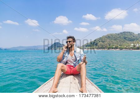 Young Man Tourist Sail Long Tail Thailand Boat Speak Cell Smart Phone Call Ocean Sea Vacation Travel Trip Exotic Holiday