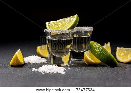 Mexican alcoholic drink tequila with salt and lemon or lime on black stone table