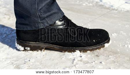 Men's leg wearing jeans and shoe. Black shoe. Black shoe in the snow.
