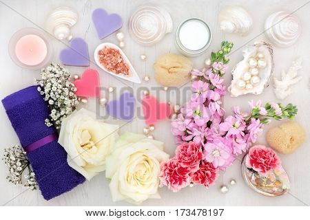 Bathroom and spa accessories with white rose, pholx and gypsophilla flowers, himalayan salt, moisturising cream, face towel, soaps, shells and pearls on distressed wood background.