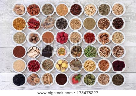 Large collection of aphrodisiac food for sexual health in china bowls on distressed wood background.