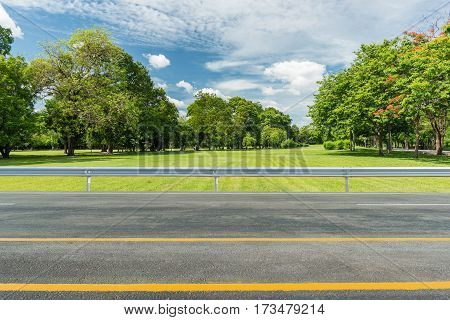 Side view of asphalt road with green grass field in park