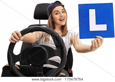 Joyful young girl showing an L-sign and sitting in a car seat isolated on white background