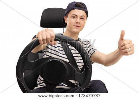 Teenager seated in a car seat holding a steering wheel and giving a thumb up isolated on white background