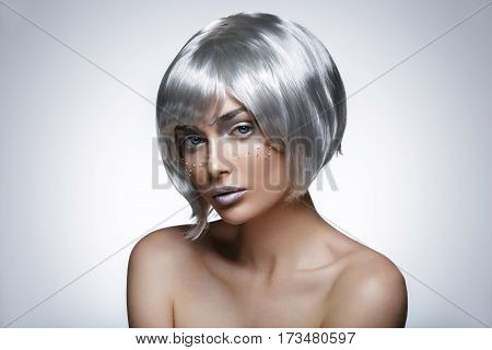 Beautiful young woman with glowing skin, fashion make-up in short silver hair wig. Beauty shot on black background. Copy space.