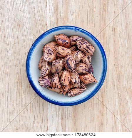 Raw Organic Pinto beans in bowl on wood floor background.
