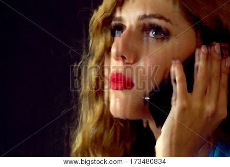 Woman talking on phone. Portrait of sad female behind window with rain. Sad woman's face looking up behind glass with drops. Black background.