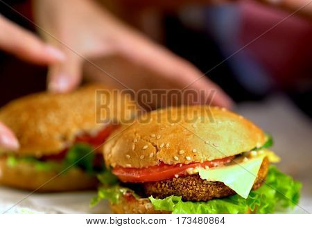 Hamburger fast food with ham on wooden board . Group of hamburger. Piece of cheese hanging from sandwich. Human hand holding cheeseburger is not in field. Fast food - nourishing eating.