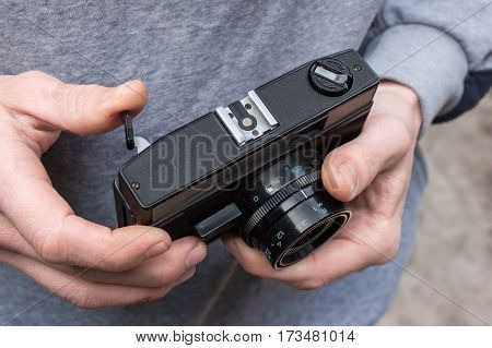 man holding two old film camera cocking the shutter
