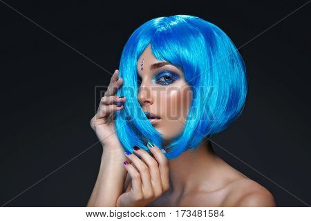 Beautiful young woman with glowing skin, fashion make-up and metallic nails in short blue wig touching hair. Beauty shot on black background. Copy space.