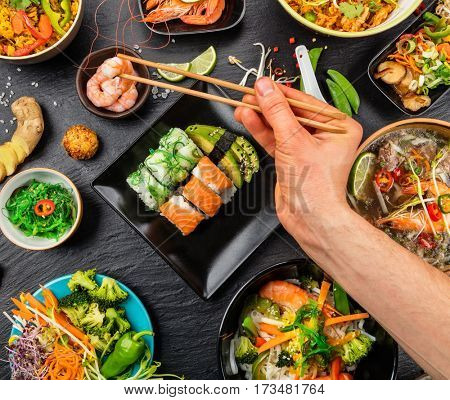 Man hand with chopsticks, eating asian food, top view. Chinese and vietnamese cuisine set.