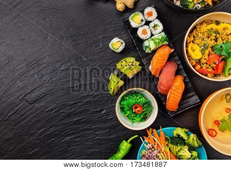 Asian food served on black stone, top view, space for text. Chinese and vietnamese cuisine set.